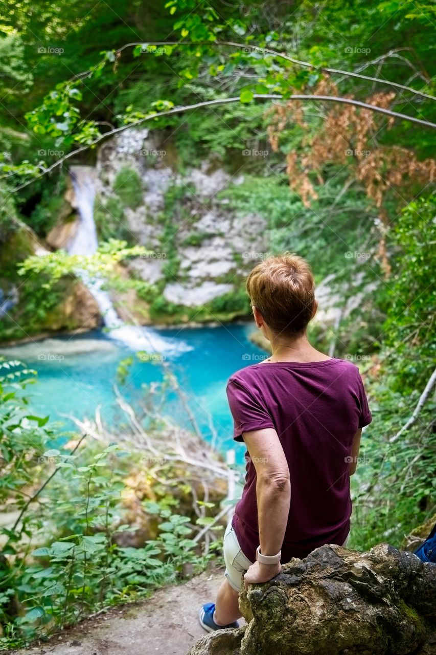 A woman contemplates a waterfall and a beautiful blue lake