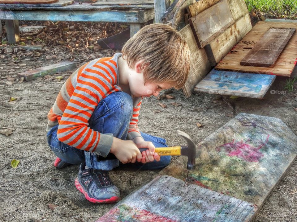 Young Boy Building A Treehouse With His Carpentry Skills. Young Boy Learning Carpentry