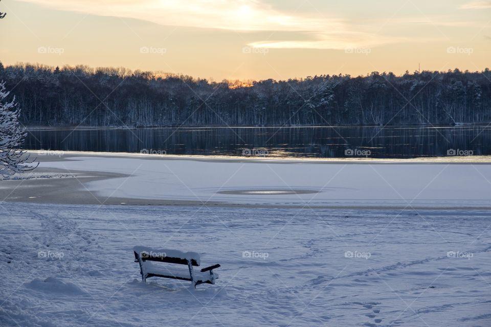 Winter wonderland, empty park bench by the lake at sunset - vinter och snö, en tom parkbänk i snöigt vinterlandskap med utsikt över sjö vid solnedgång