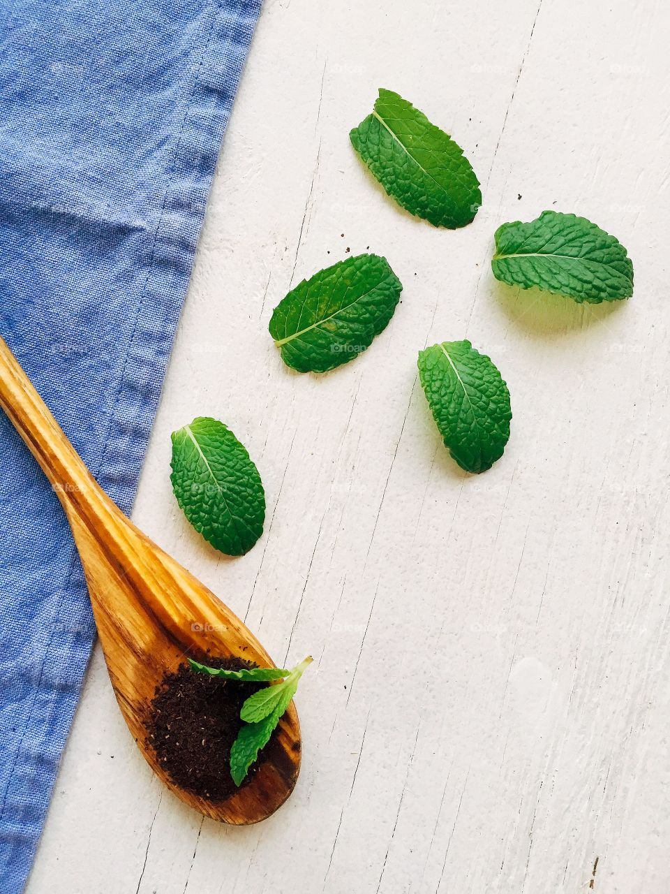 Dried tea leaves on wooden spoon with mint leaves