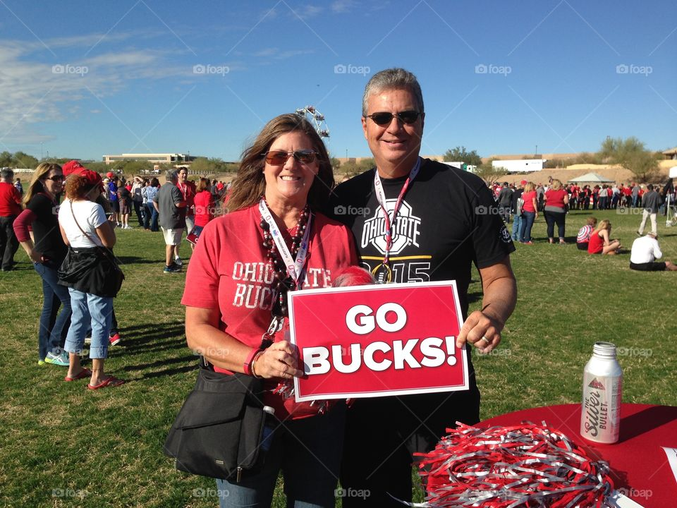 Man and woman holding cardboard with go bucks text