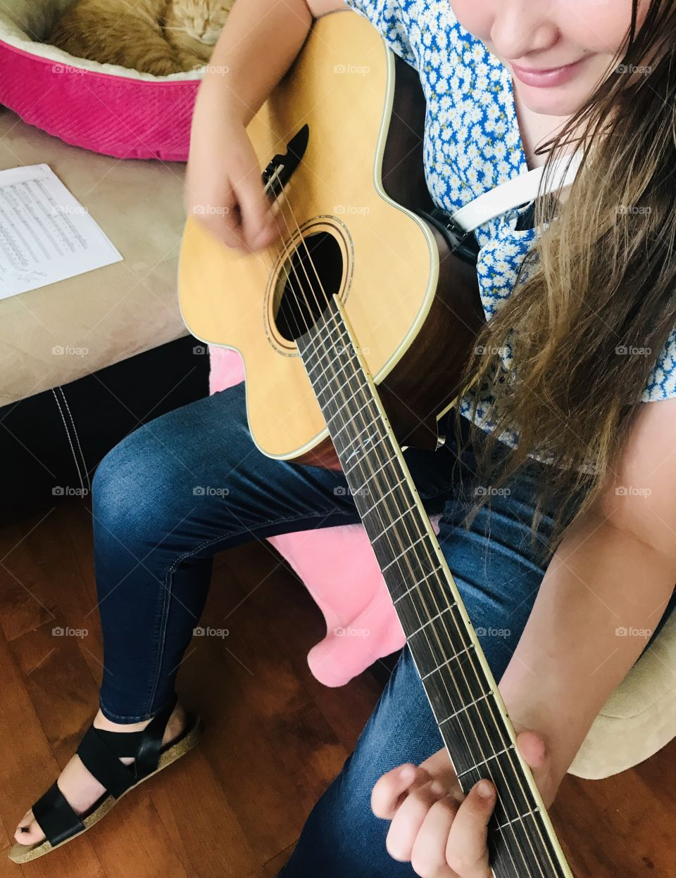 Young girl smiling as she strums on her favorite guitar with her kitty sitting with her in background.