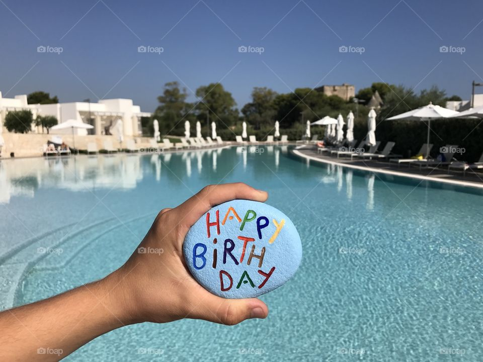 Happy Birthday stone front of a swimming pool