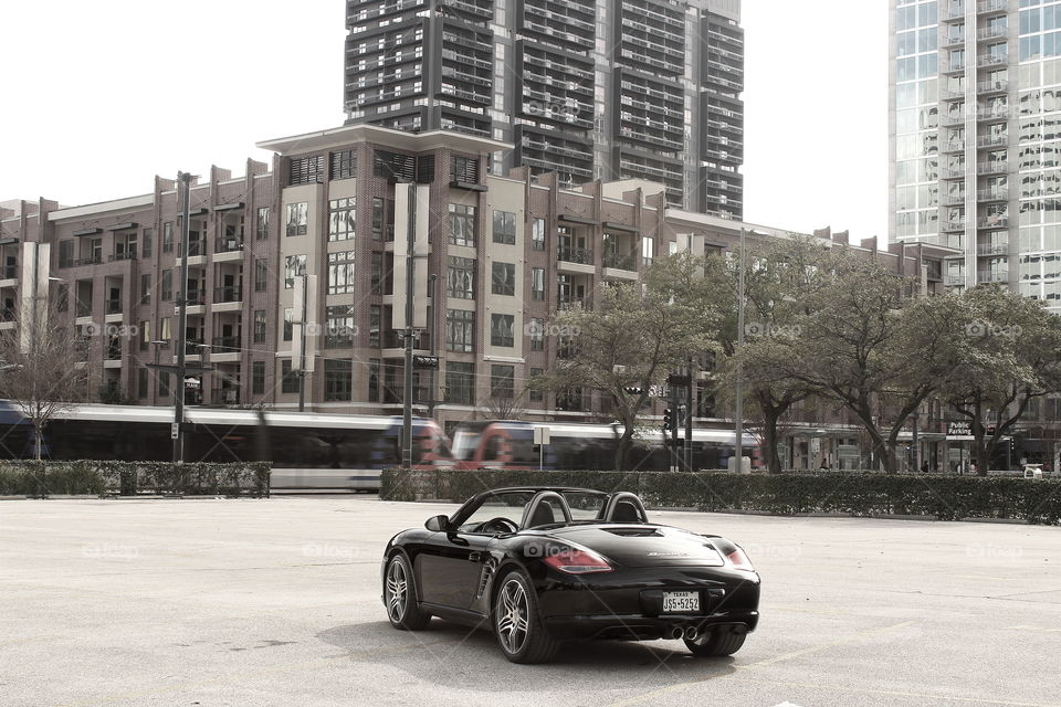 Black porsche convertible in city with moving train, unsaturated