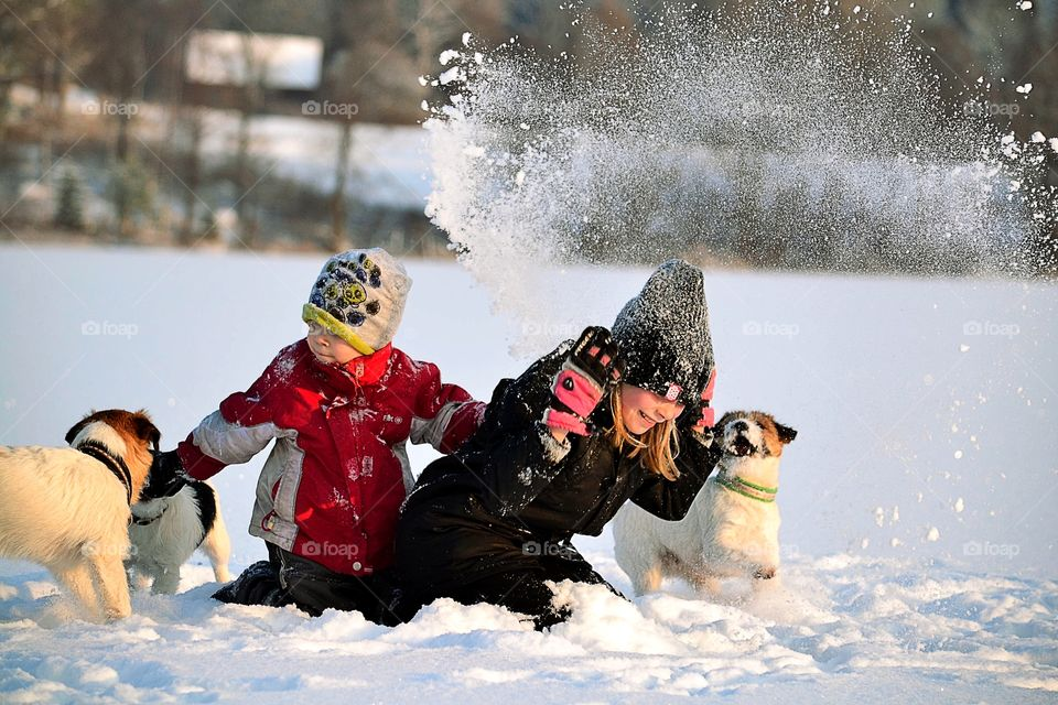 Brother and sister enjoying with dogs in snow
