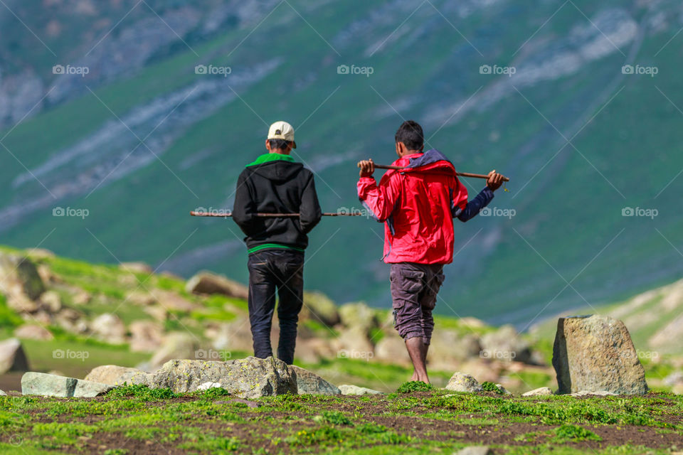 two people or shepherds walking with sticks on their shoulder and talking briefly