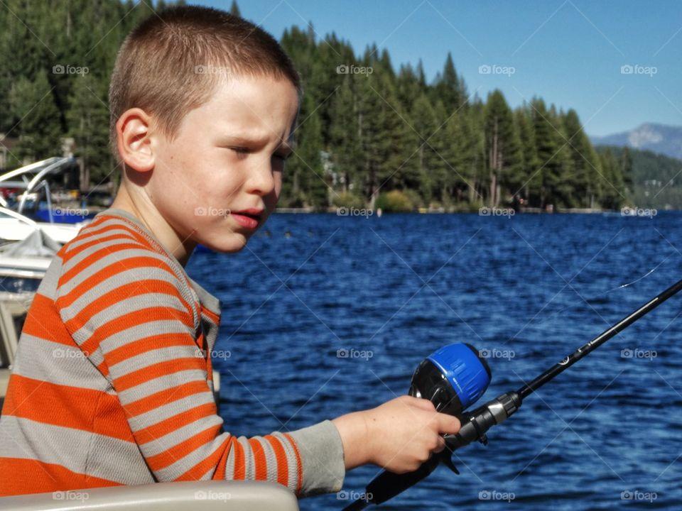 Little boy holding fishing rod on the lake