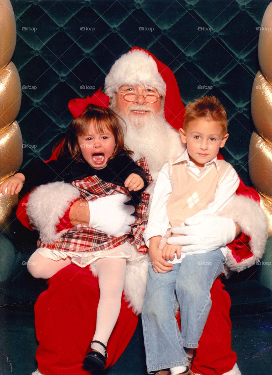 Santa Claus carrying two kids