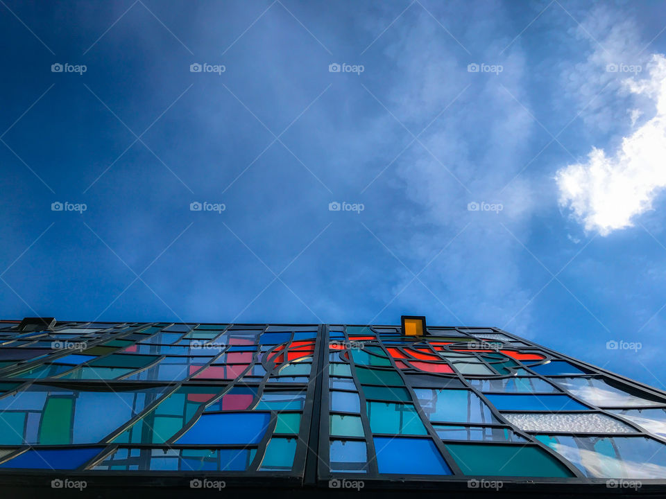Colorful stained glass greenhouse against blue clear sky