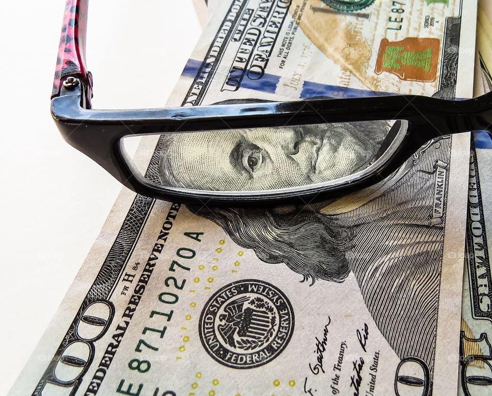 Eyeglasses on dollars banknote