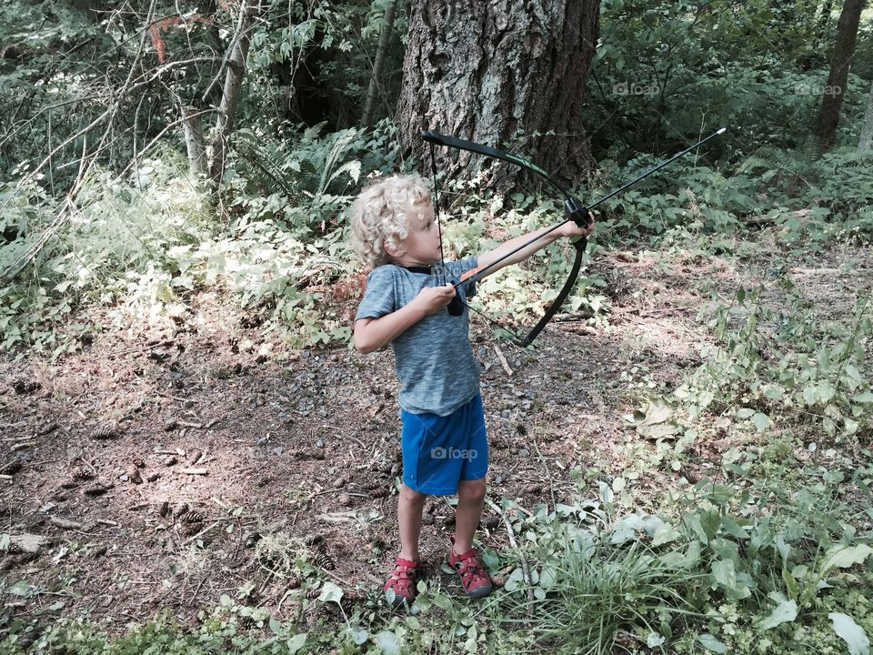 Little boy shooting bow . A little boy stands in the woods shooting a bow and arrow