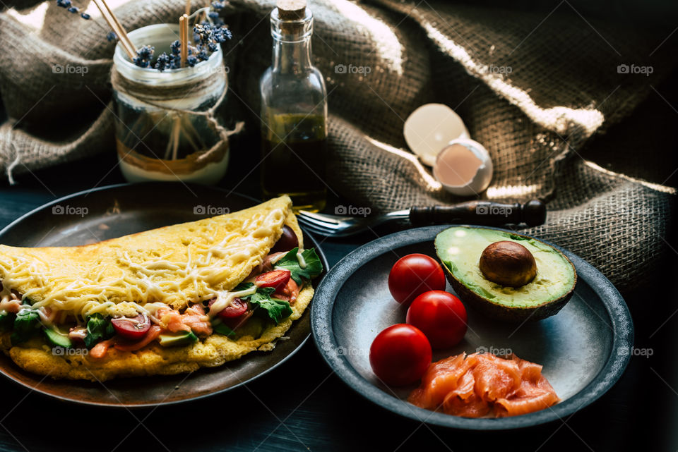 fresh, fluffy omelette with salmon, tomatoes, avocado, cheese and rucola, on a wooden rustic table