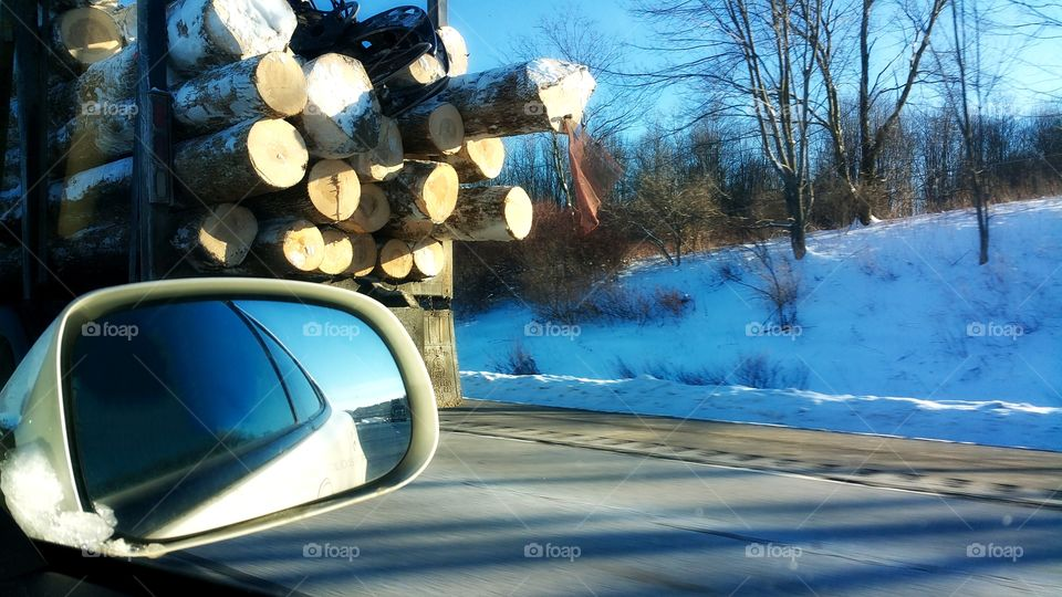 riding down the highway passing a logging truck