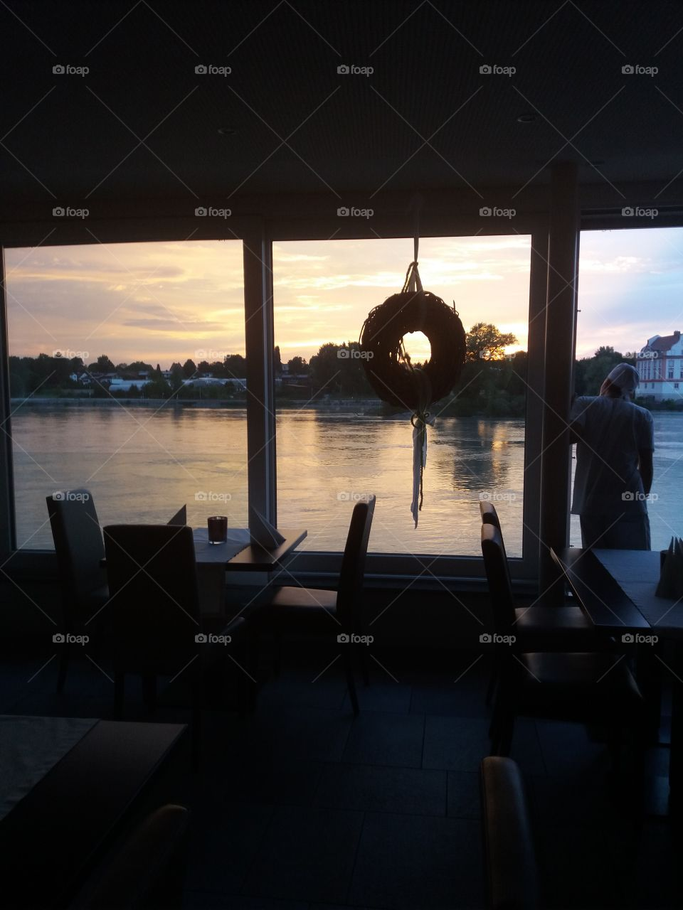 From a restaurant hall, a photo of an Austrian river at the sunset with German confine on the other side of the river. In first plan tables and chairs for customers.