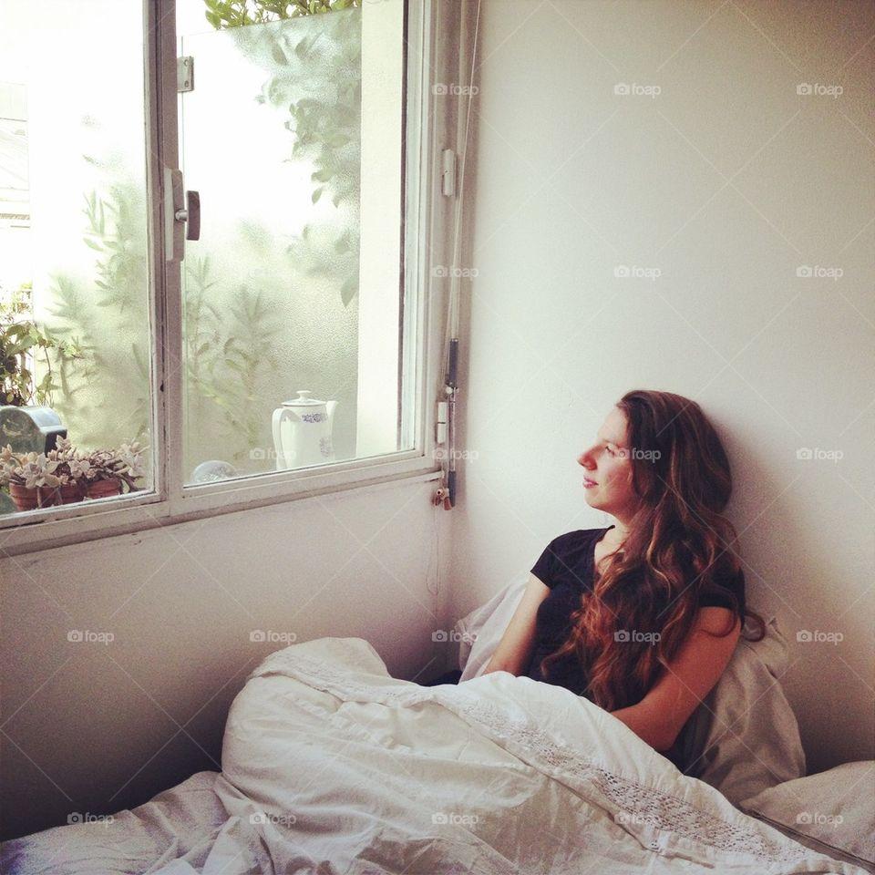 Girl on white bright bedroom