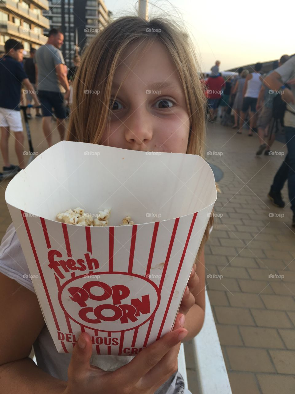 Girl holding popcorn in hand