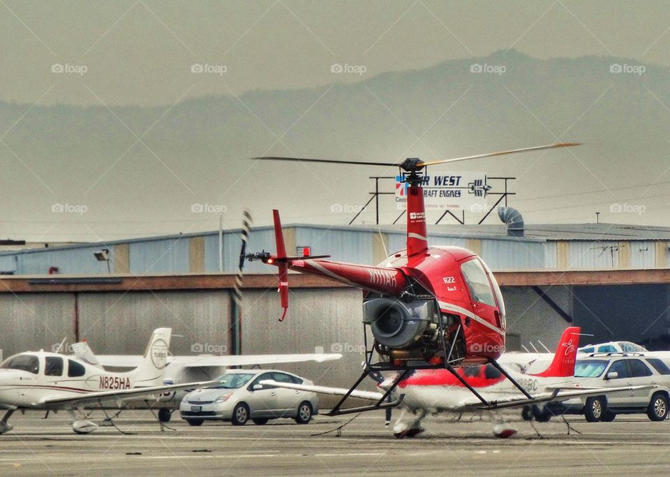 Helicopter Preparing For Liftoff. Robinson R-22 Helicopter Hovering Over An Airfield