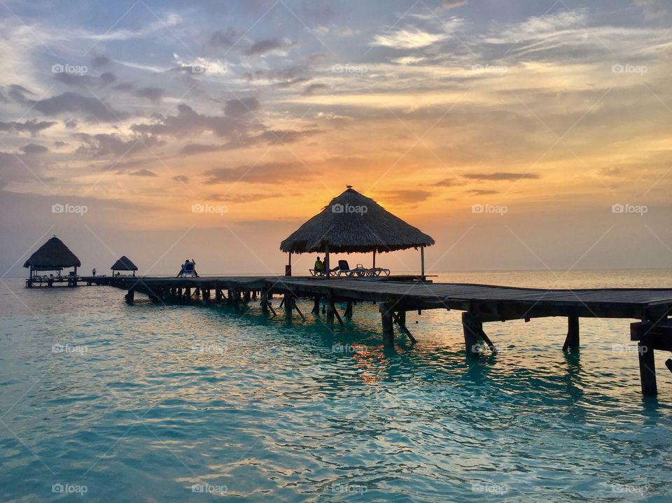 Wooden bridge in sea at sunset