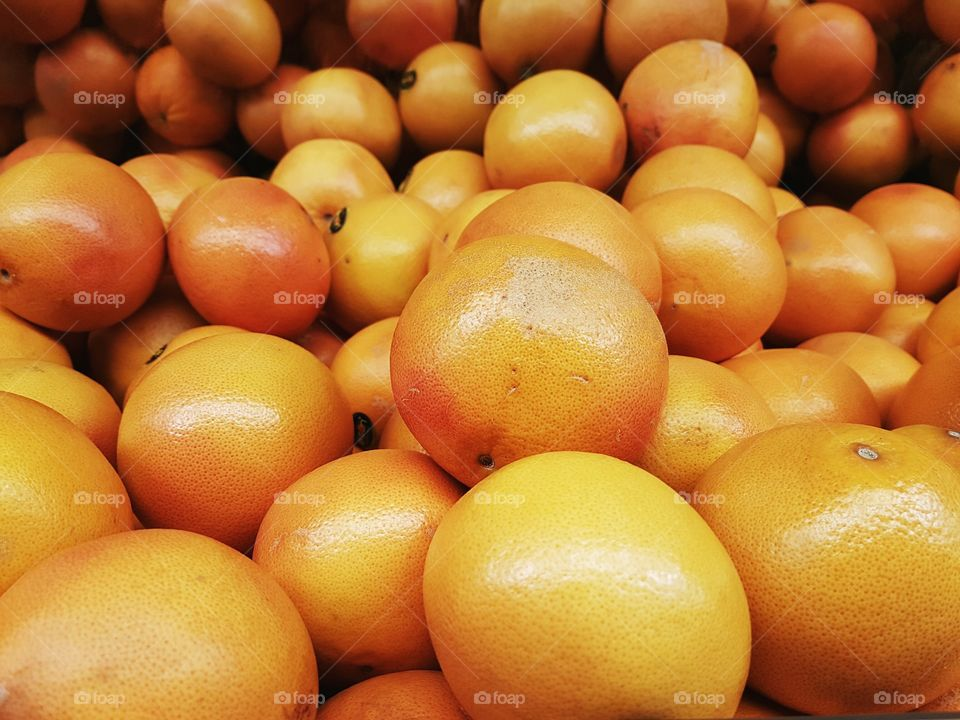 Orange grapefruits stacked and grouped on display shelves for sale