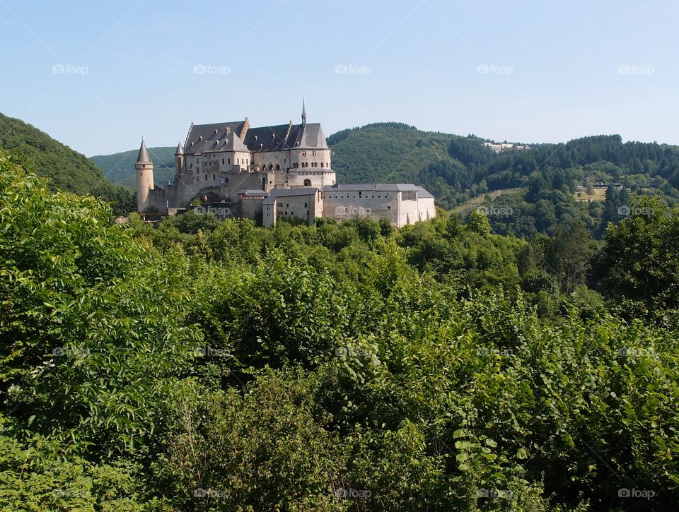 Chateau Vianden in Luxembourg sits amongst the green hills on a summer day.