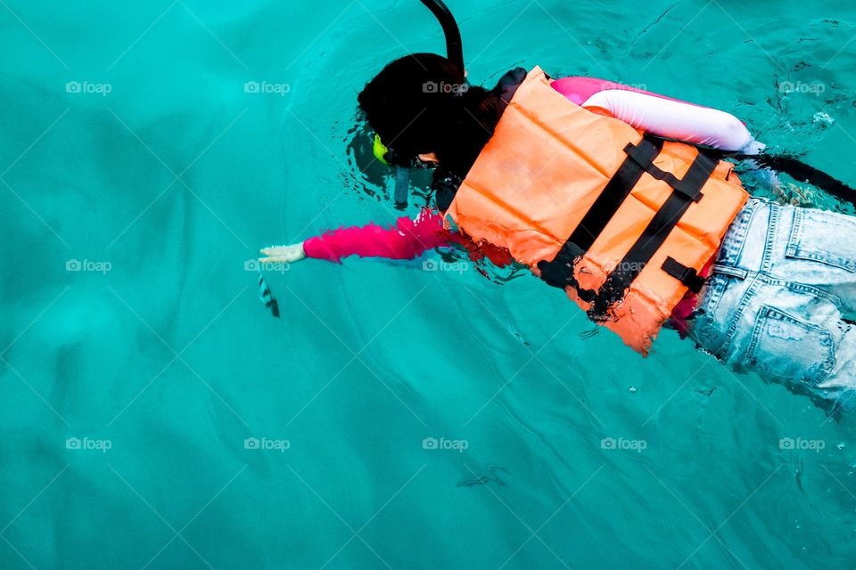 Snorkeling girl trying to reach a fish in the sea with her hand