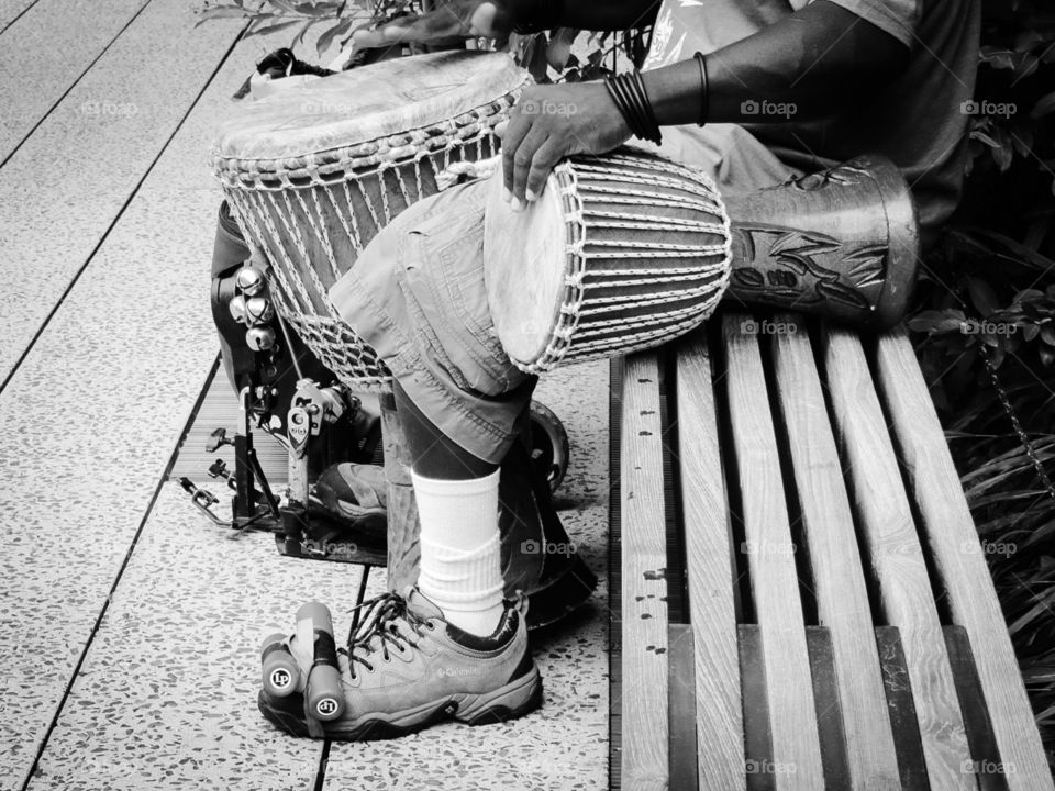 Music Man. A street musician in New York, performing as a one-man band for passers by, playing on drums, done in black & white