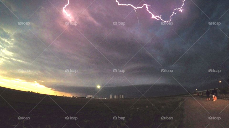 Supercell thunderstorm over the plains of northeastern Colorado. A lightning bolt creeps through the sky.