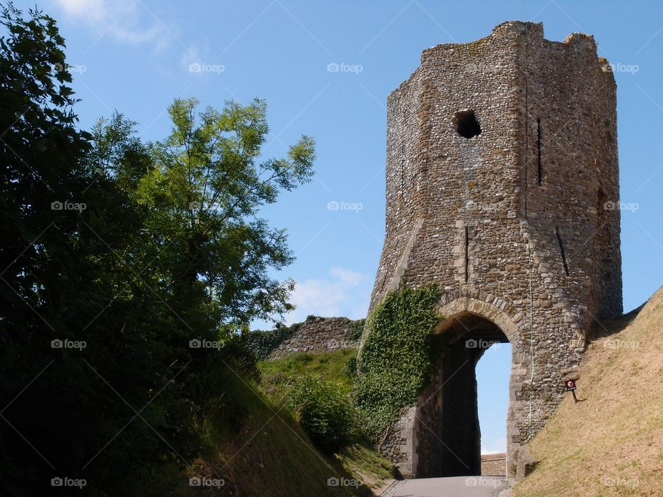 A large stone tower at Dover Castle with an arched entryway and a hole for archers to fire arrows with a walkway leading tourists to it on a warm and sunny summer day in England.