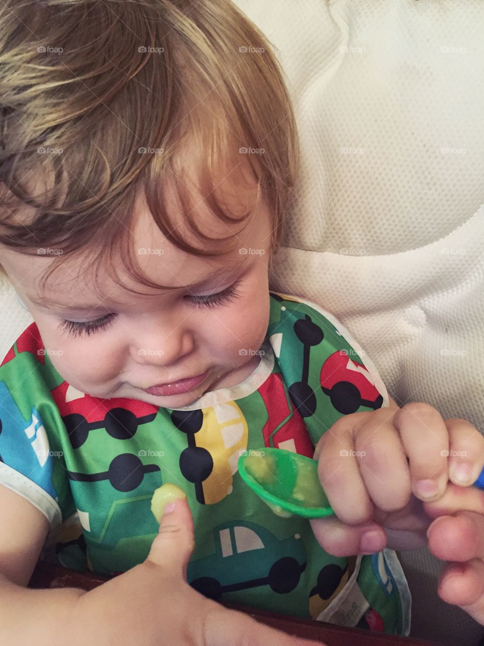 Cute toddler holding spoon with cream on thumb