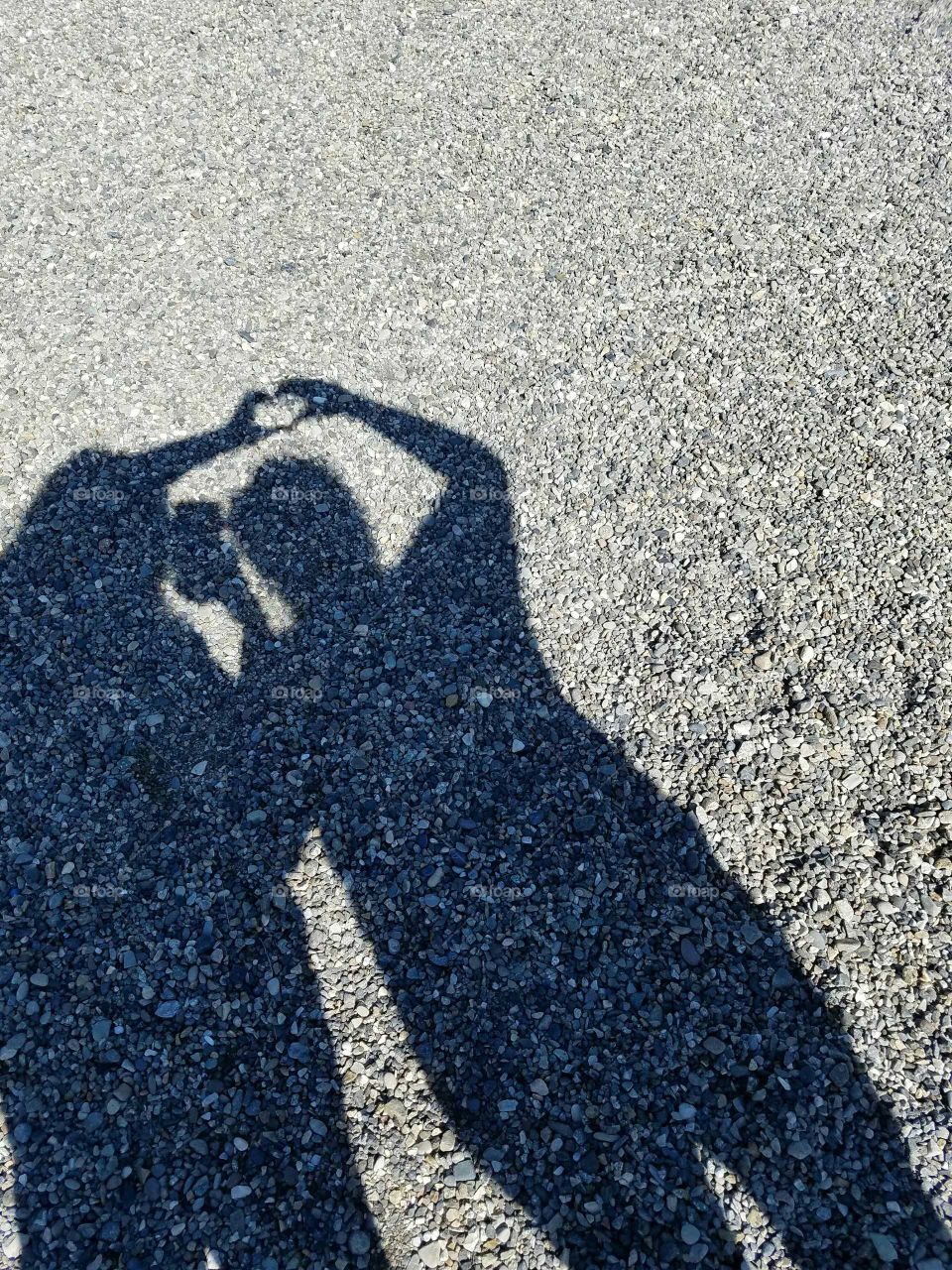 Shadow of two people making heart shape