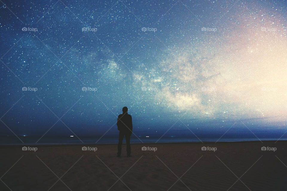 Silhouette of a man looking at milky way in sky