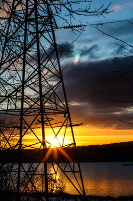 Electricity pylon near lake during sunset