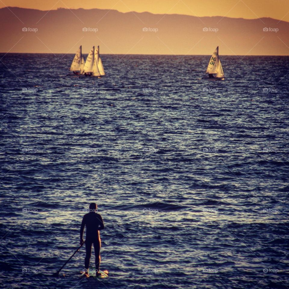 Paddleboarder and sailships