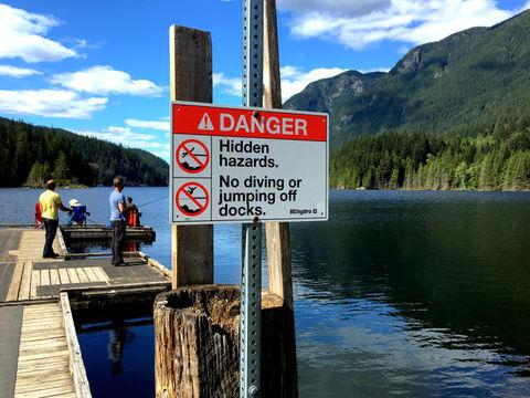 Fishing at the lake and hazard sign