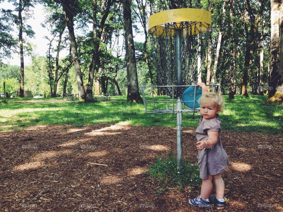 Cute Little Girl Playing Disc Golf