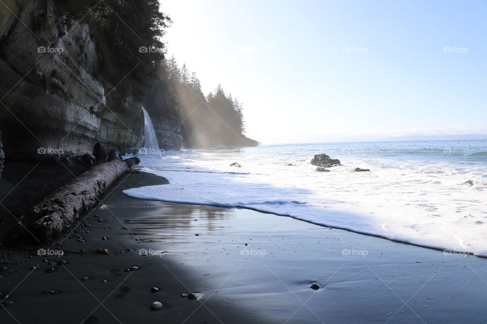 Calm sandy beach during low tide ,crashed waves  slowly bubbling on the shore and waterfall from surrounding forest