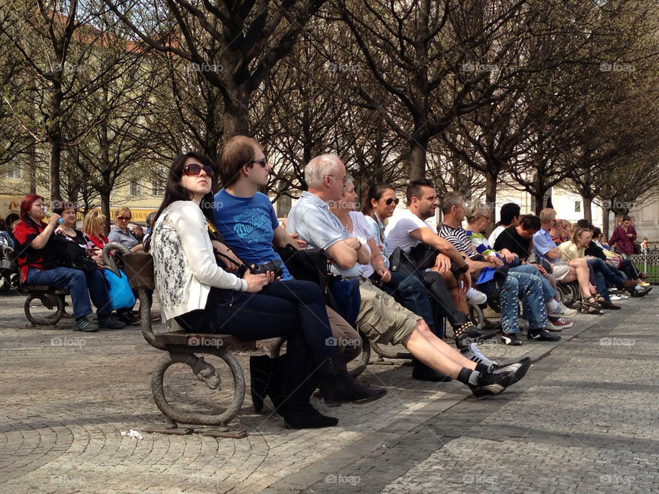 Public sitting in benches relaxing in town square