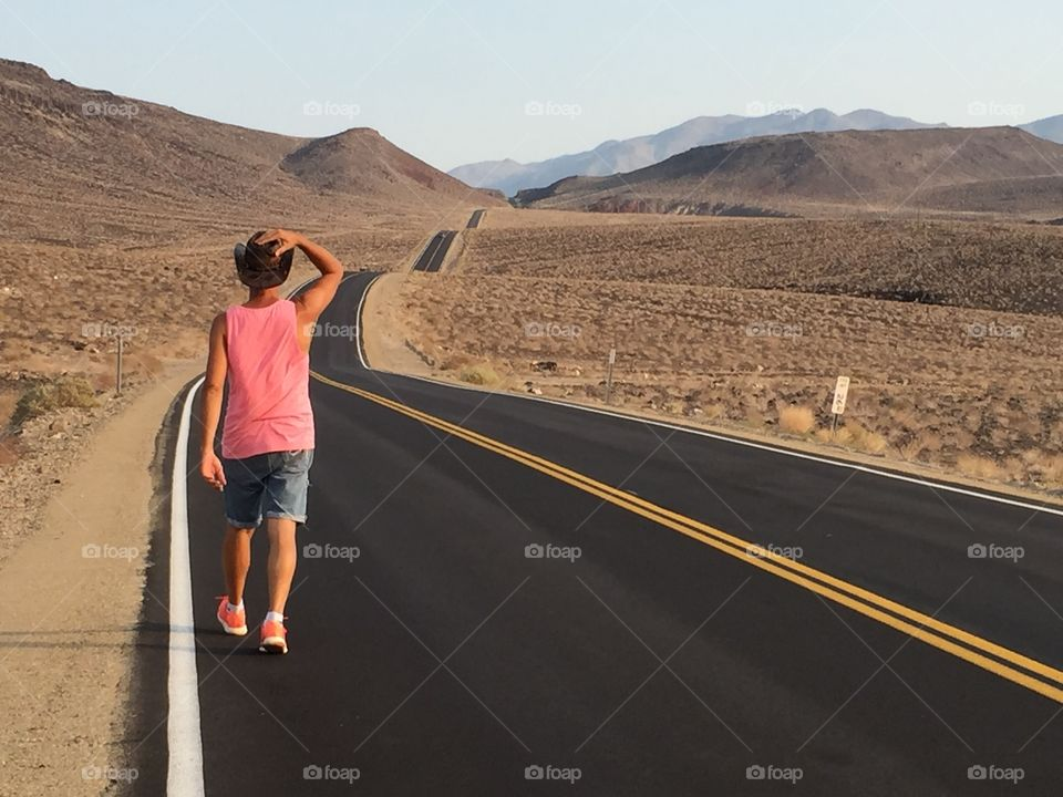 Man walks alone in a beautiful valley on a amazing road placed beside the Death valley