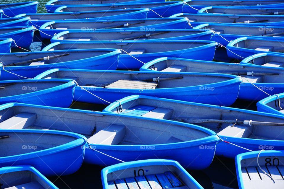 Blue tourist boats moored for the end of season at Arashiyama.
