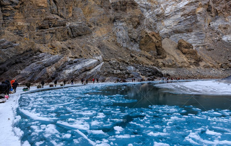 group of wanderlust trekkers walking in a line by the frozen lake and floating ice