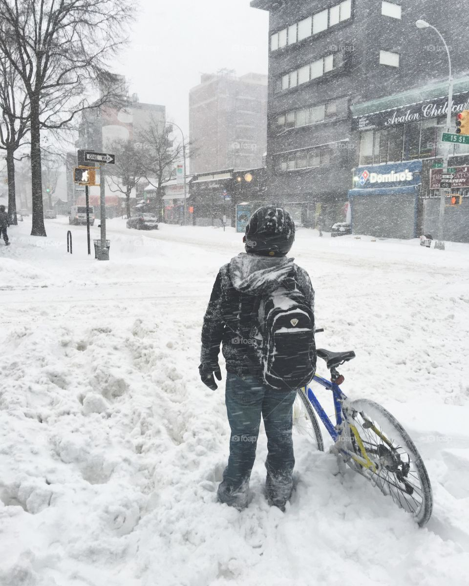 Boy pushing his bicycle through snow drifts in Blizzard Jonas inPark Slope, Brooklyn, New York.