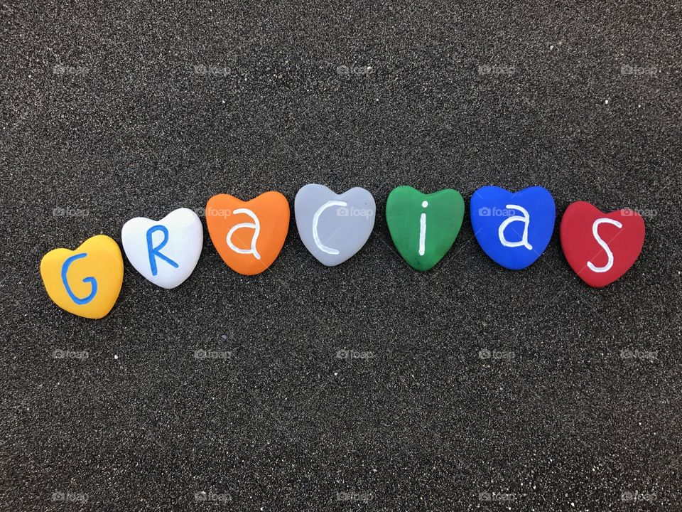 Gracias word with colored heart stones over black volcanic sand