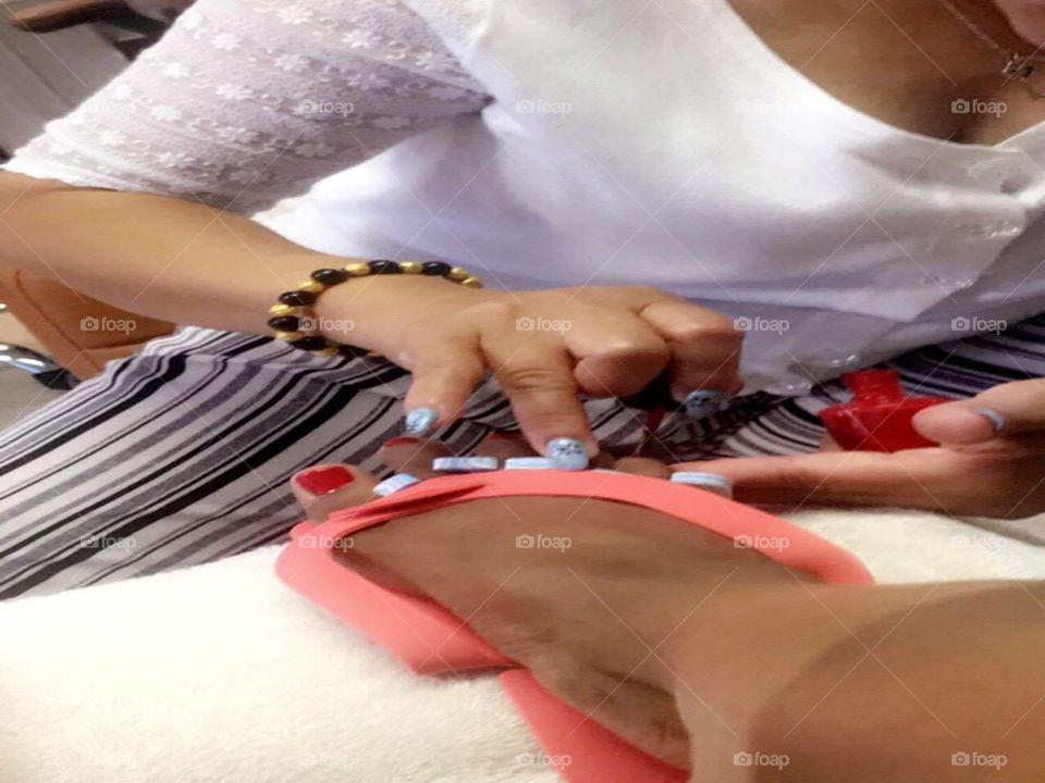 Girl getting her toe nails polished red