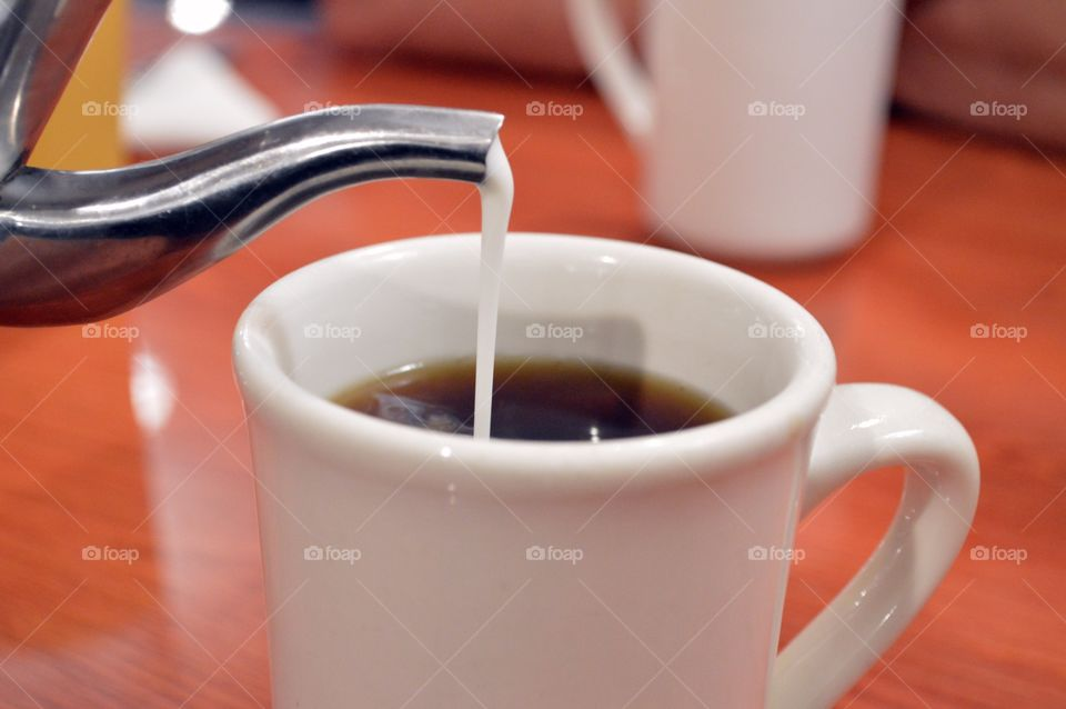 Pouring milk in a cup of coffee