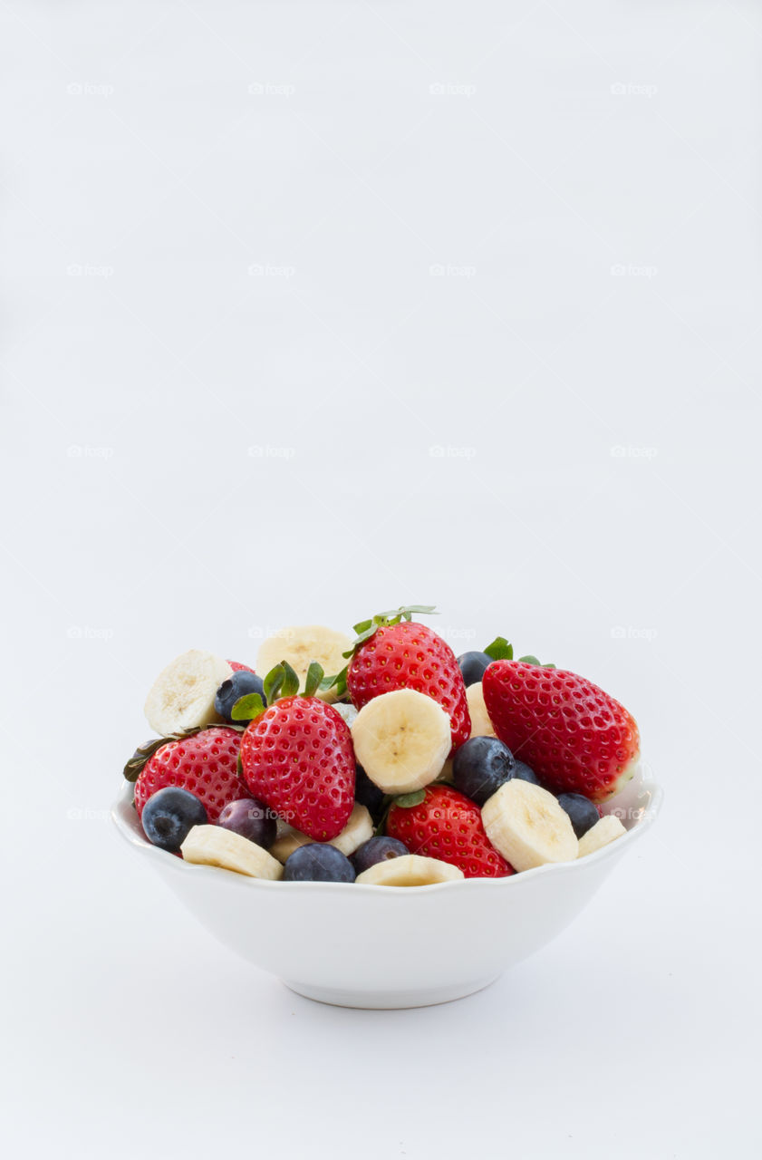 Berry fruits with banana slices in bowl
