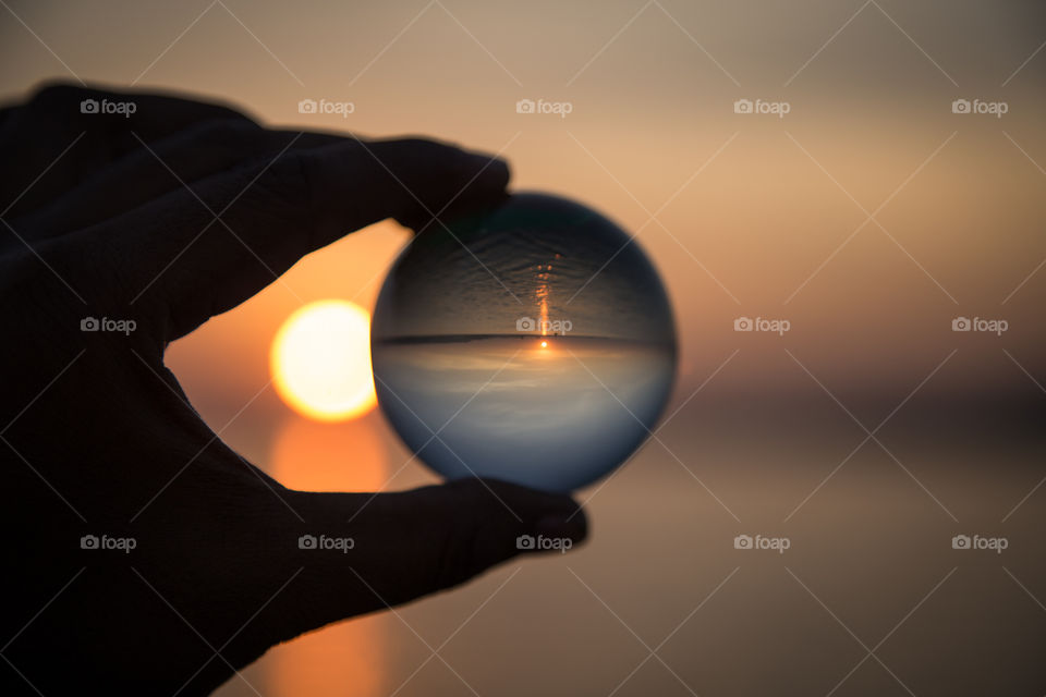 A person holding crystal ball during sunset