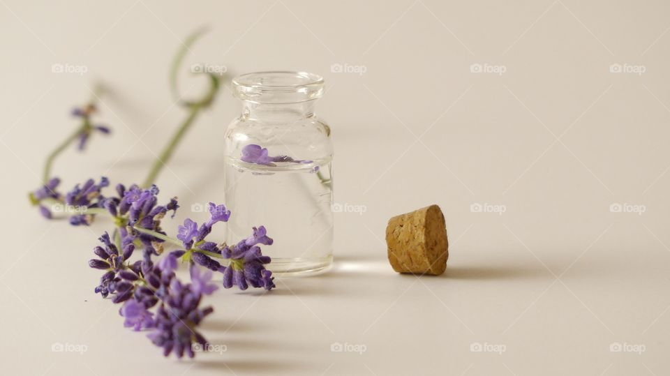 Glass jar with oil and lavender flowers