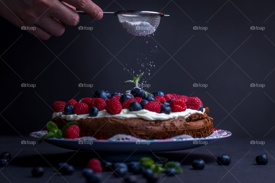 Person's hand holding strainer over the cake