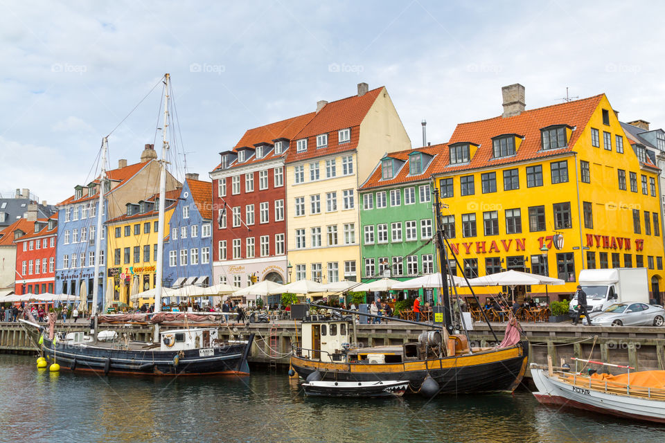 Nyhavn area in Copenhagen, Denmark. Colorful houses and sailboats. Nordic design. Touristic and famous spot. Water and cloudy sky. Restaurants next to the water