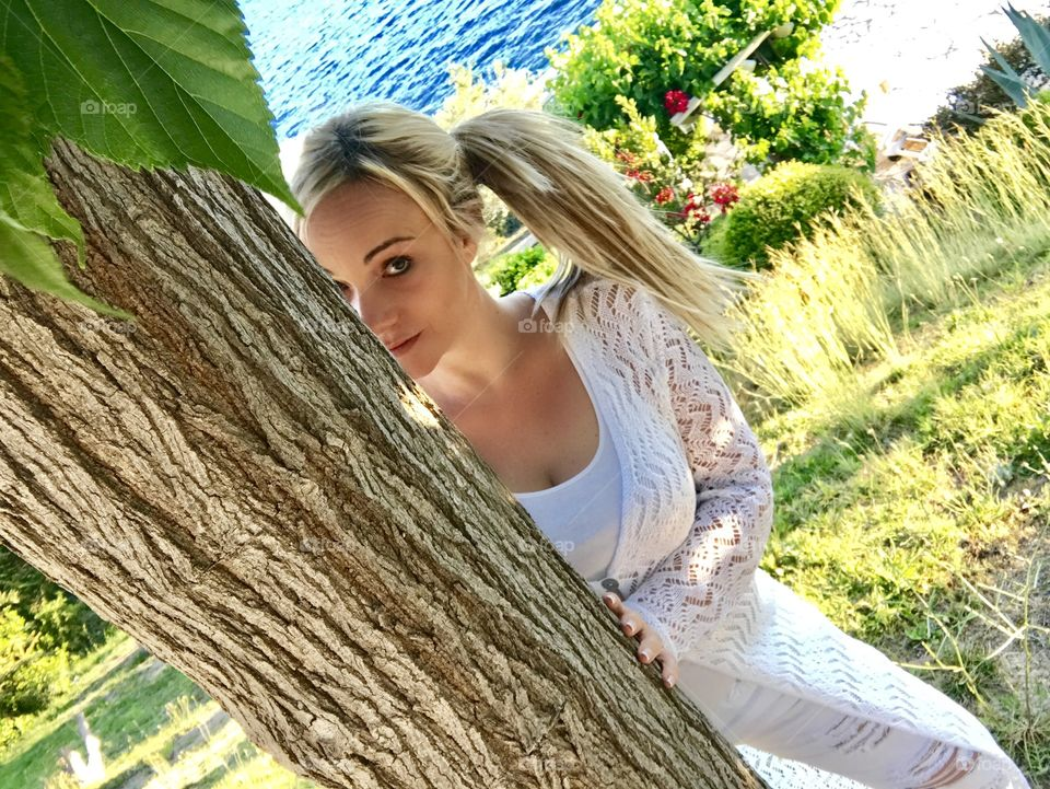 Young woman looking from behind the tree
